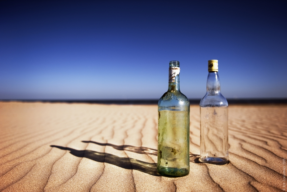A piece of fine art art photography titled Bottles On Sand by Wim Schuurmans