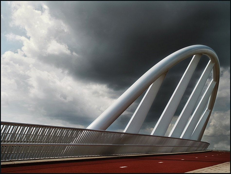 A piece of fine art art photography titled Bridge Under Troubled Sky by Paula Loonen