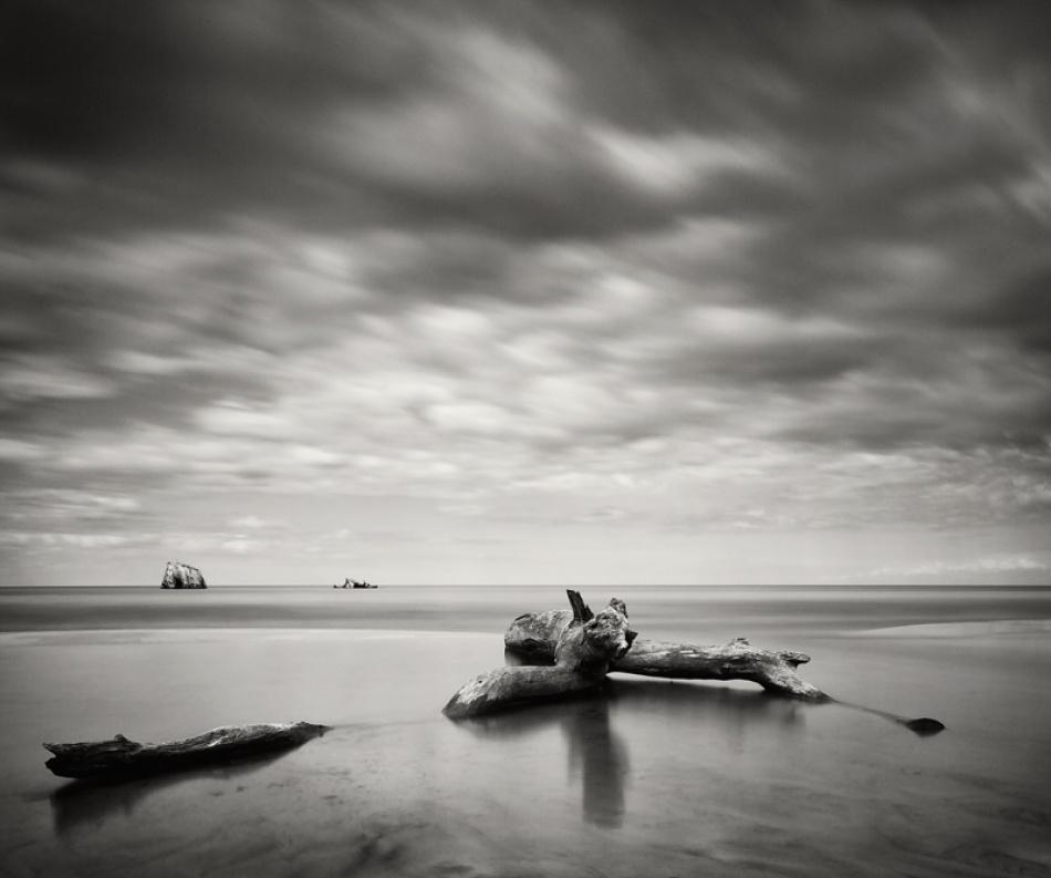 A piece of fine art art photography titled Driftwood and Shipwreck by Armands Belakovs-Ceimers
