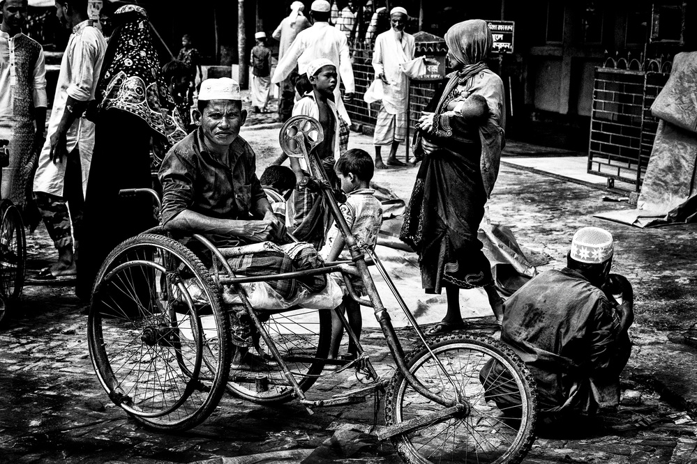 A piece of fine art art photography titled Asking for Some Help Outside a Mosque After Friday Prayers - Bangladesh by Joxe Inazio Kuesta Garmendia