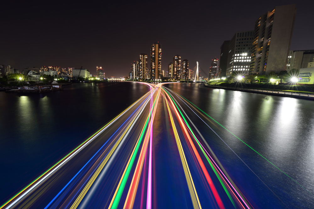 A piece of fine art art photography titled Light Trace of Houseboats and the Rivercity21 Towers by Yasushi Okumura