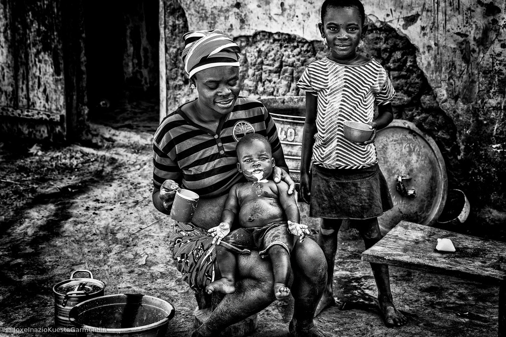 View this piece of fine art photography titled Feeding her child with milk - Benin by Joxe Inazio Kuesta Garmendia