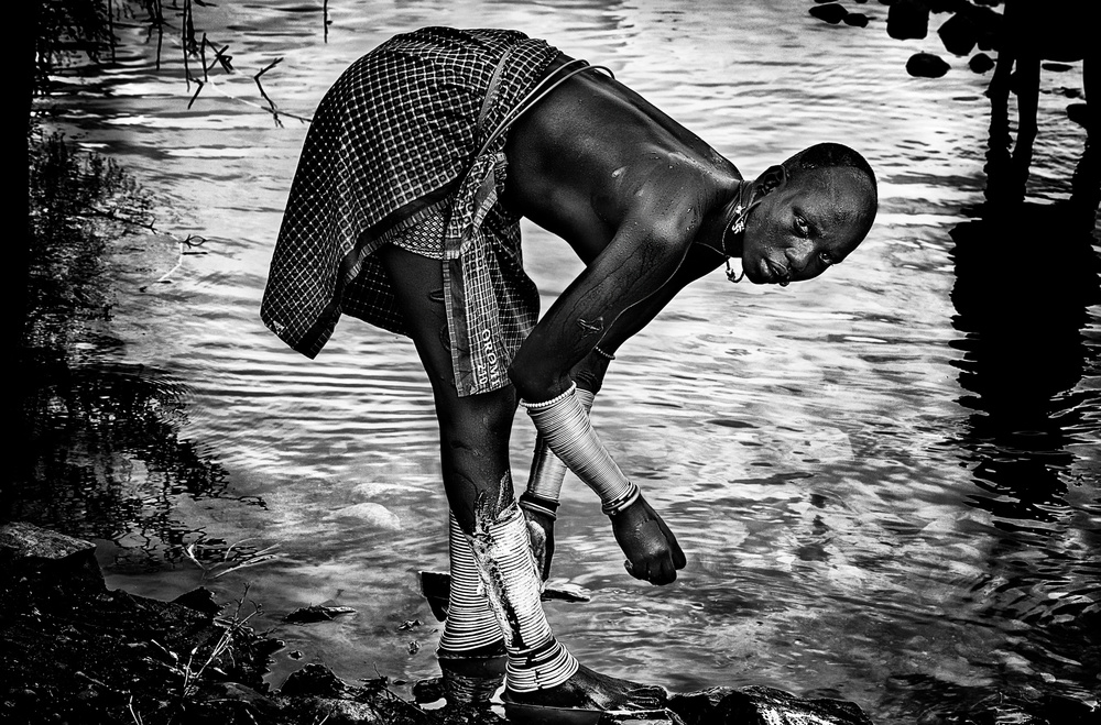 A piece of fine art art photography titled Surma Tribe Woman Washing Up Her Jewelry - Ethiopia by Joxe Inazio Kuesta Garmendia
