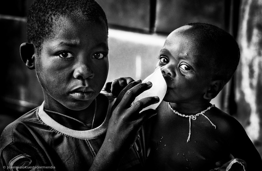 Quenching his brother´s thirst with a frozen water bag - Benin