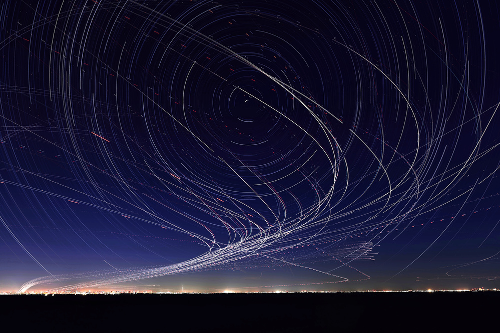 A piece of fine art art photography titled Startrails and Planetrails Over the Tokyo Bay by Yasushi Okumura