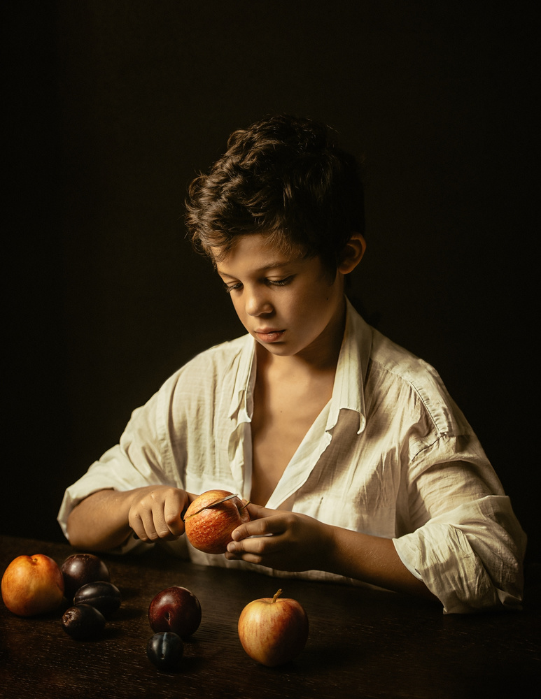 A piece of fine art art photography titled Boy Peeling a Fruit by Monot Samuel