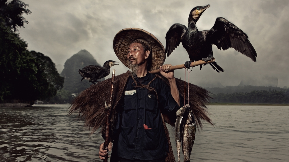 A piece of fine art art photography titled A Chinese Fisherman With His Two Cormorants by Glenn Meling