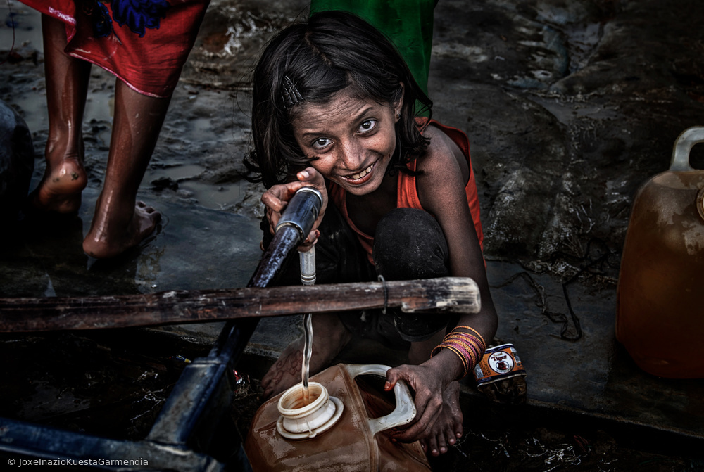 View this piece of fine art photography titled Rohingya refugee girl filling a container of water - Bangladesh by Joxe Inazio Kuesta Garmendia