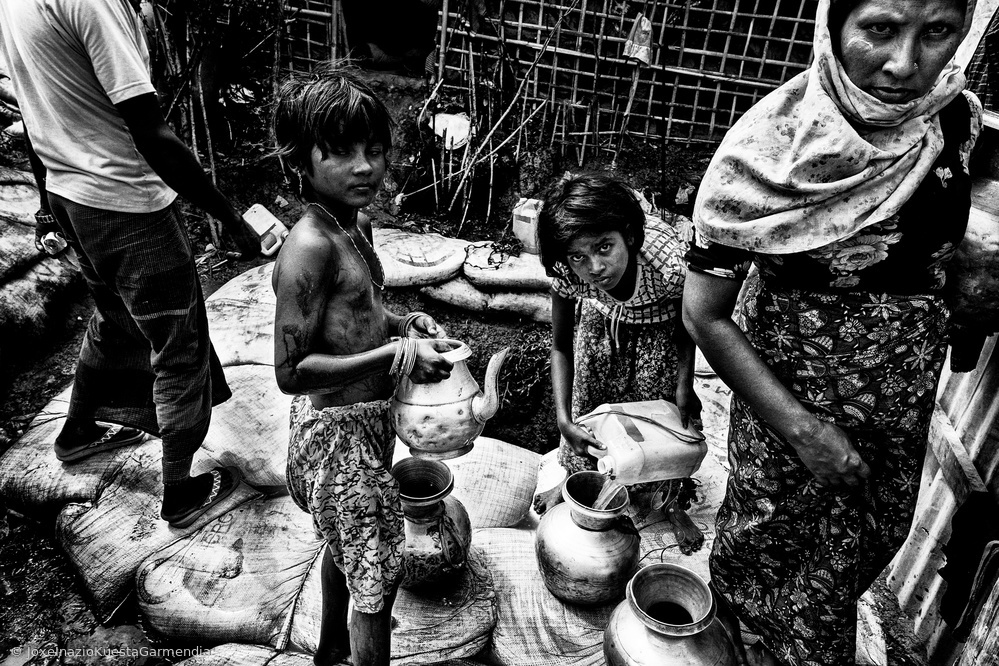 Rohingya people drawing water from a pit - Bangladesh