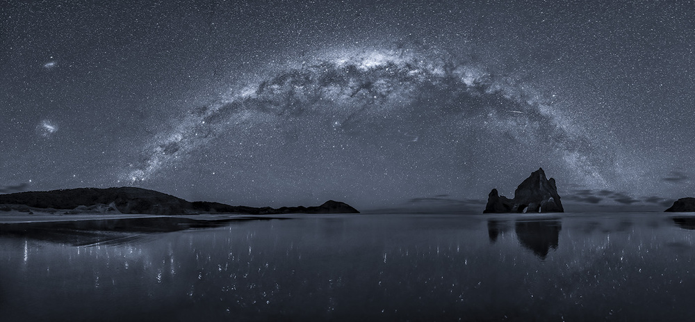 A piece of fine art art photography titled The Milky Way Over Wharariki Beach by Hua Zhu