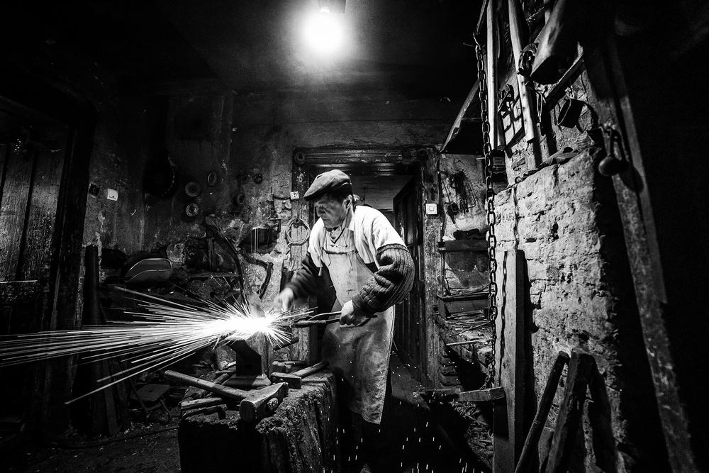 A piece of fine art art photography titled Nicu, the Blacksmith from Transylvania by Sebastiæn