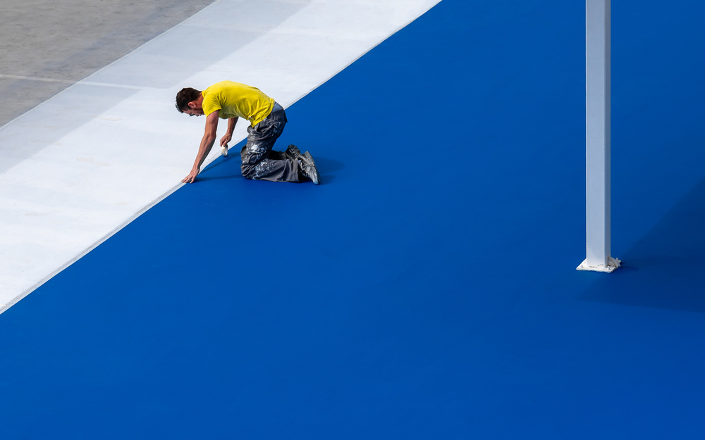A piece of fine art art photography titled Worker In Yellow On Blue and White by Harry Lieber