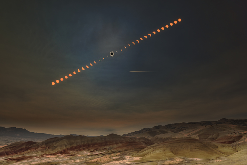 A piece of fine art art photography titled Painted Hills With Solar Eclipse by Wenjie Qiao