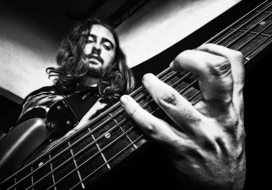 A piece of fine art art photography titled Ale Playing Bass by Sergio Bertolini