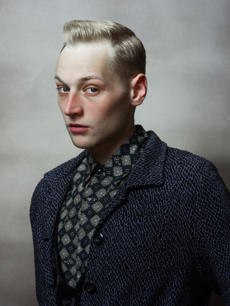 A vulnerable portrait of a well-dressed young man