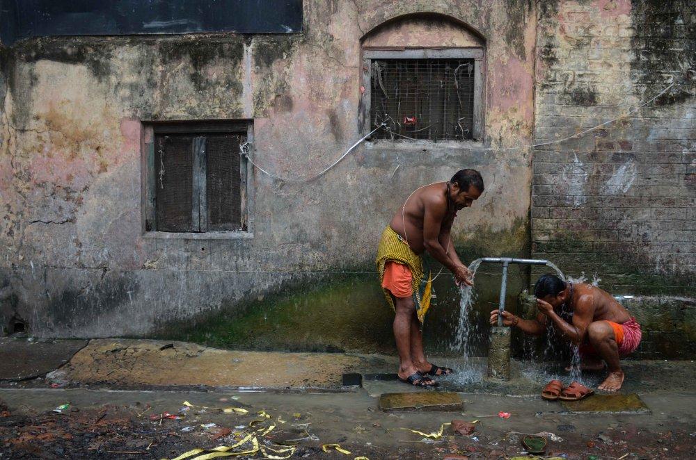 A piece of fine art art photography titled Roadside Bath by Sudipto Kumar Ghosh