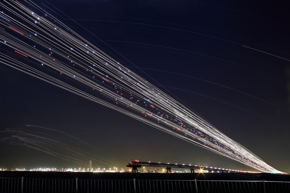 A piece of fine art art photography titled Startrails and Planetrails Over the Haneda Airport by Yasushi Okumura